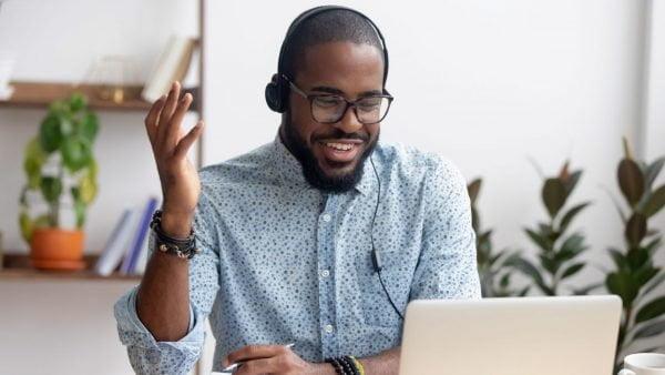 Smiling man at laptop doing webinar