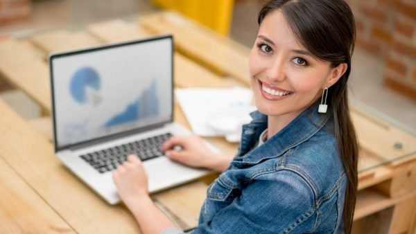 Happy woman working at the office using her laptop and looking at the camera smiling